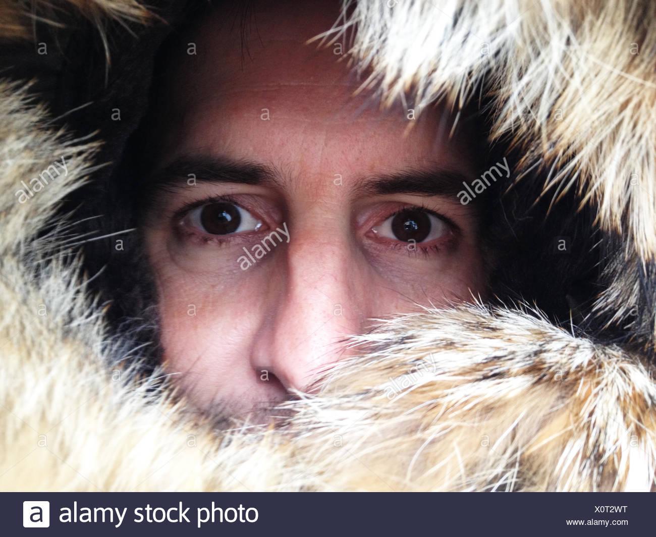 Retrato del hombre mirando a través de capucha forrada de pieles Imagen De Stock