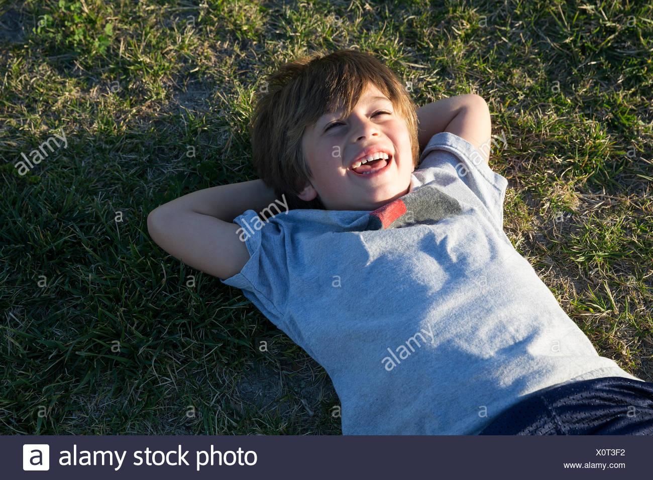 Retrato de niño acostado sobre la hierba del parque y riendo Imagen De Stock