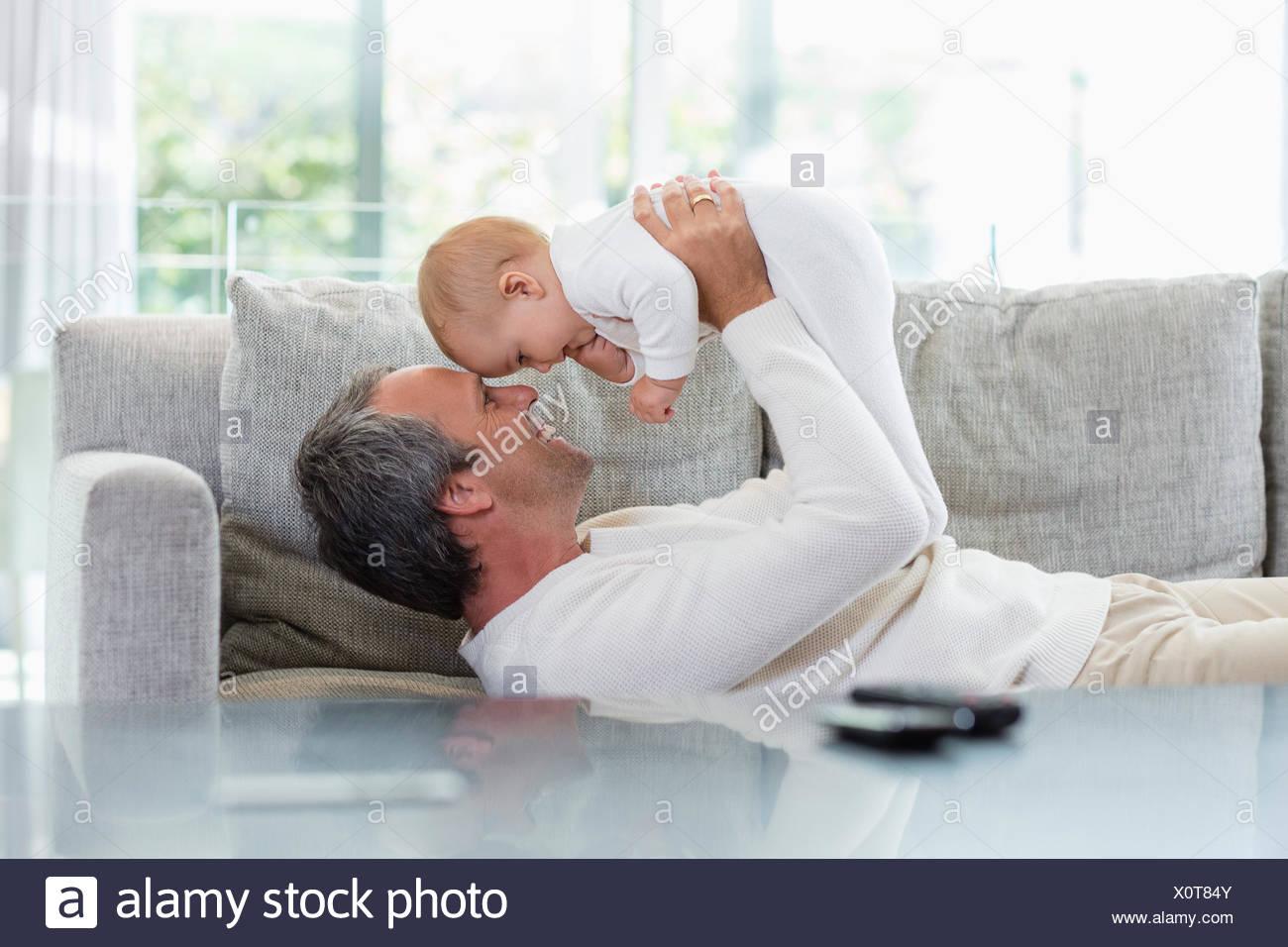 Padre feliz jugando con su linda hija en casa Foto de stock