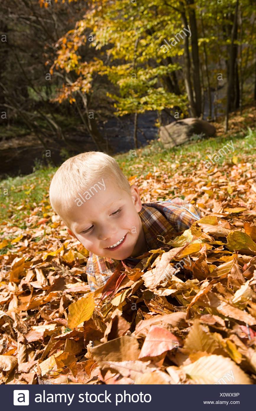 Niño jugando en hojas de otoño Foto de stock