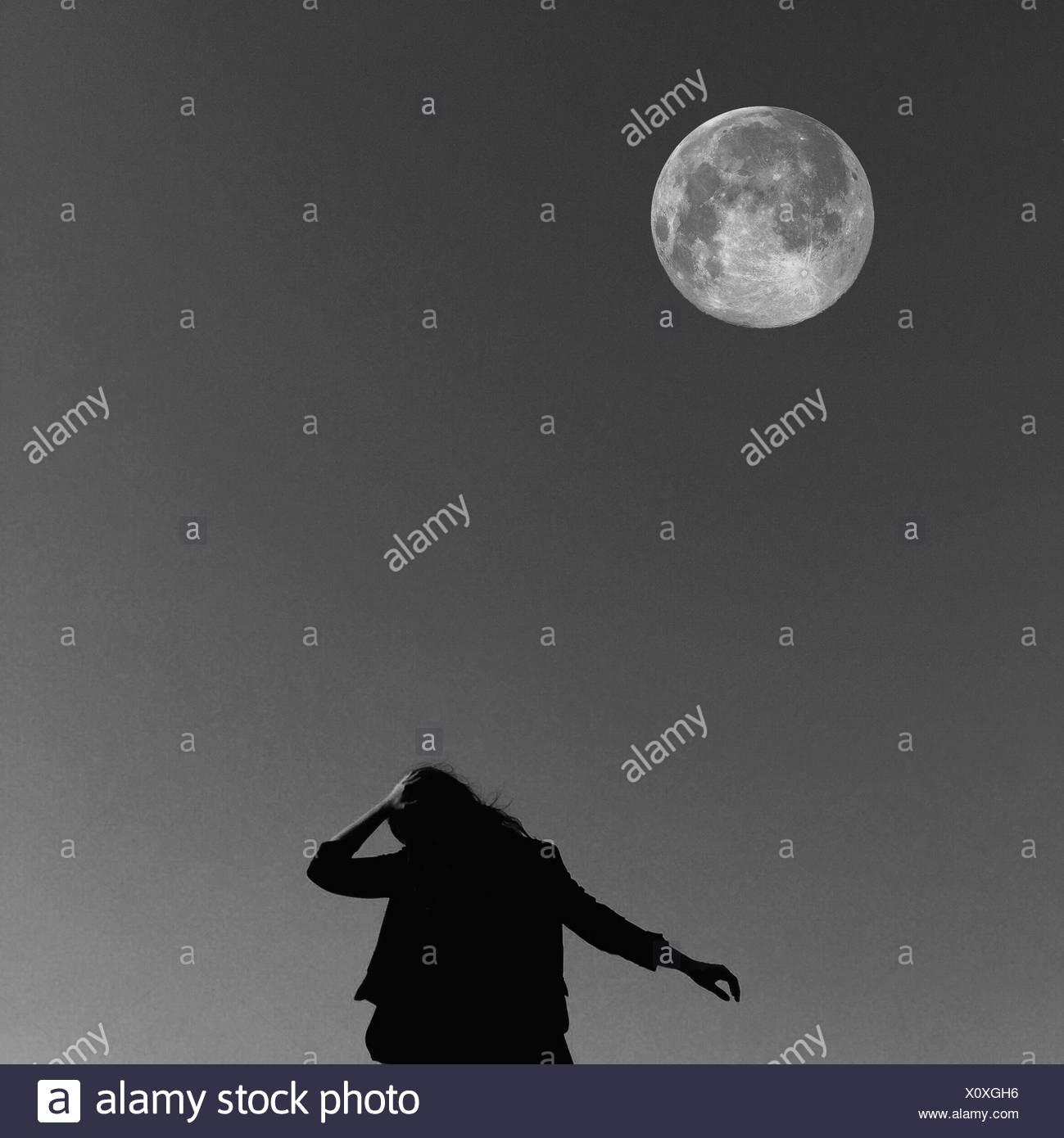 Ángulo de visión baja de la mujer contra la Luna Imagen De Stock