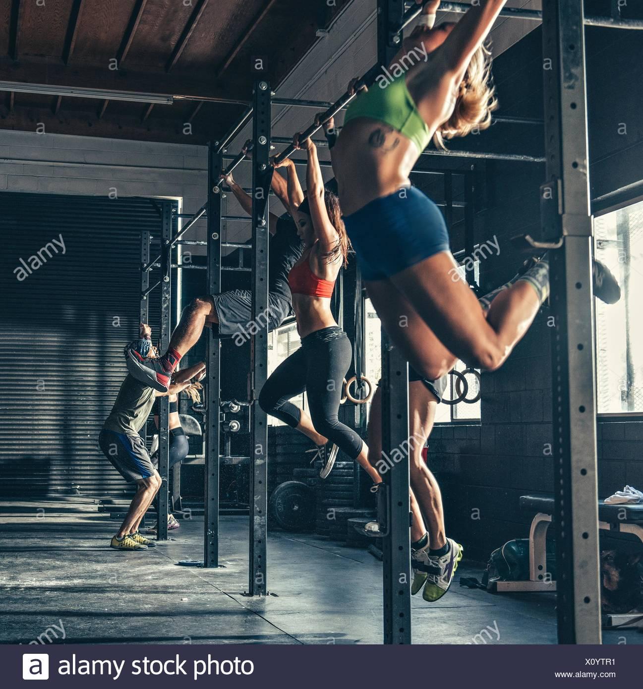 Fila de personas capacitación en barra de ejercicio en el gimnasio Imagen De Stock