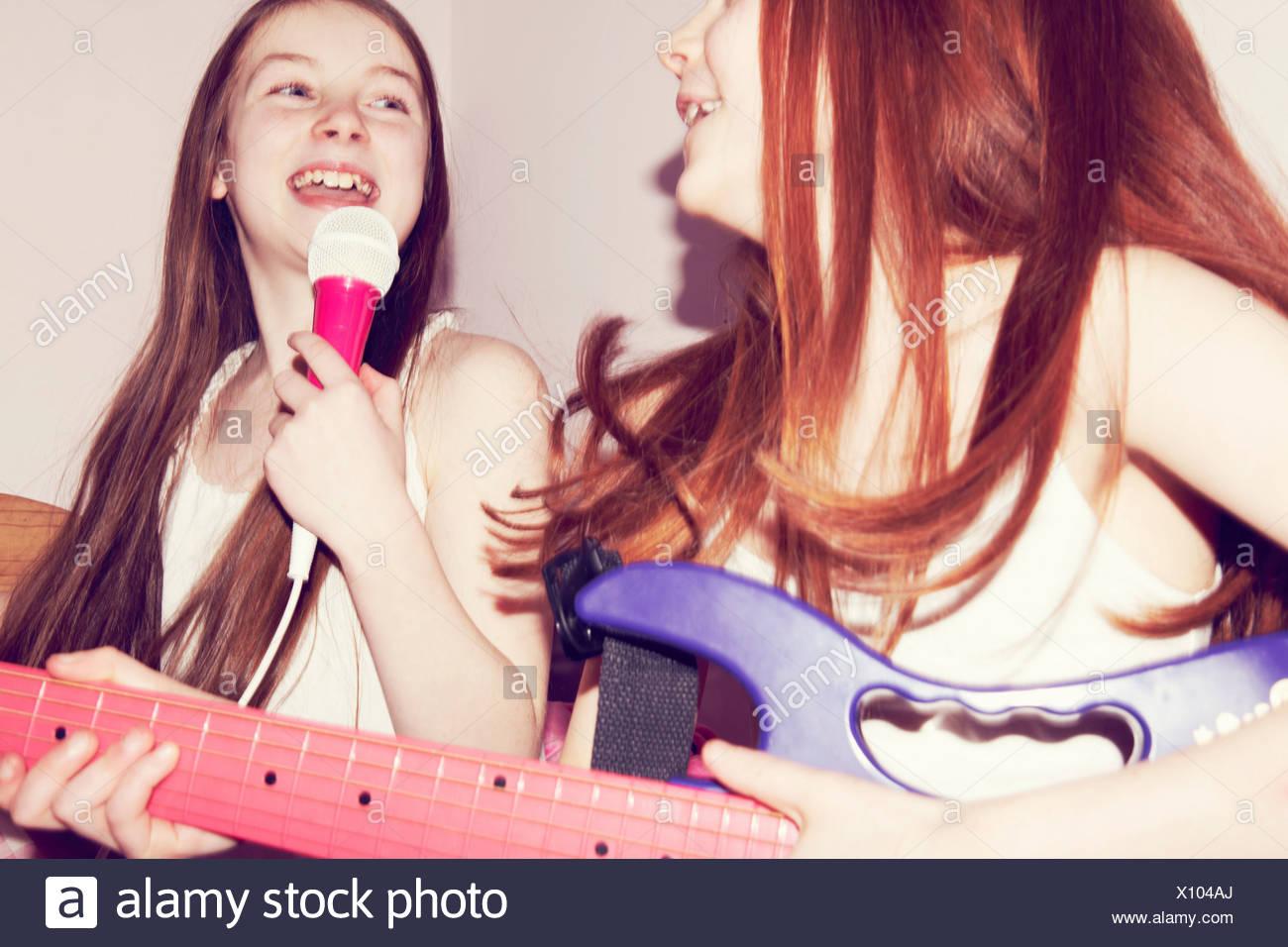 Dos niñas tocando la guitarra y cantando en el micrófono en el dormitorio Imagen De Stock