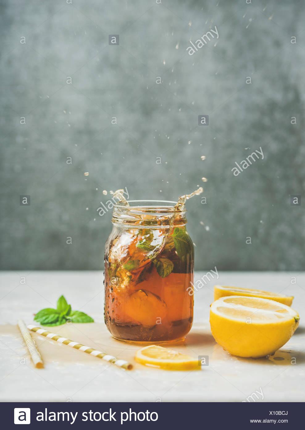 Verano frío helado de té con menta fresca, de bergamota y limón en tarro de vidrio con las salpicaduras sobre la mesa de luz, gris muro de hormigón en el fondo, copia el espacio. Los alimentos Imagen De Stock