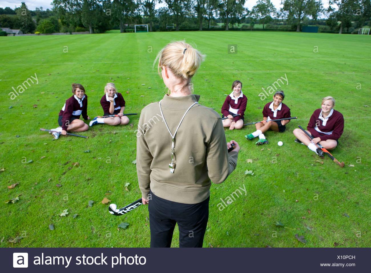 Entrenador de pie ante una adolescente del equipo de hockey de campo Imagen De Stock