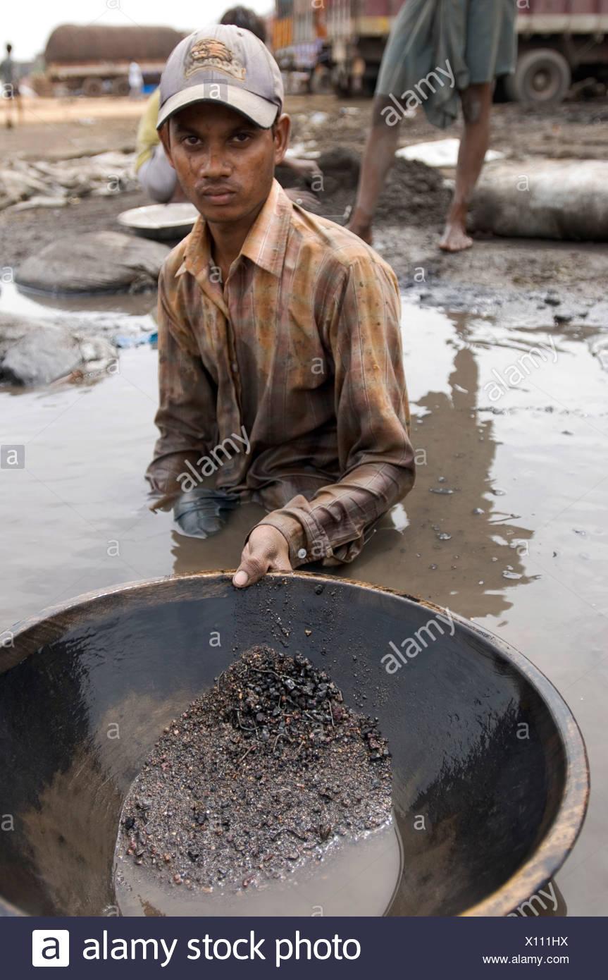 Muchos habitantes de tugurios se ganan la vida reciclando residuos industriales, este trabajador está lavando los desechos industriales tóxicos para co Imagen De Stock
