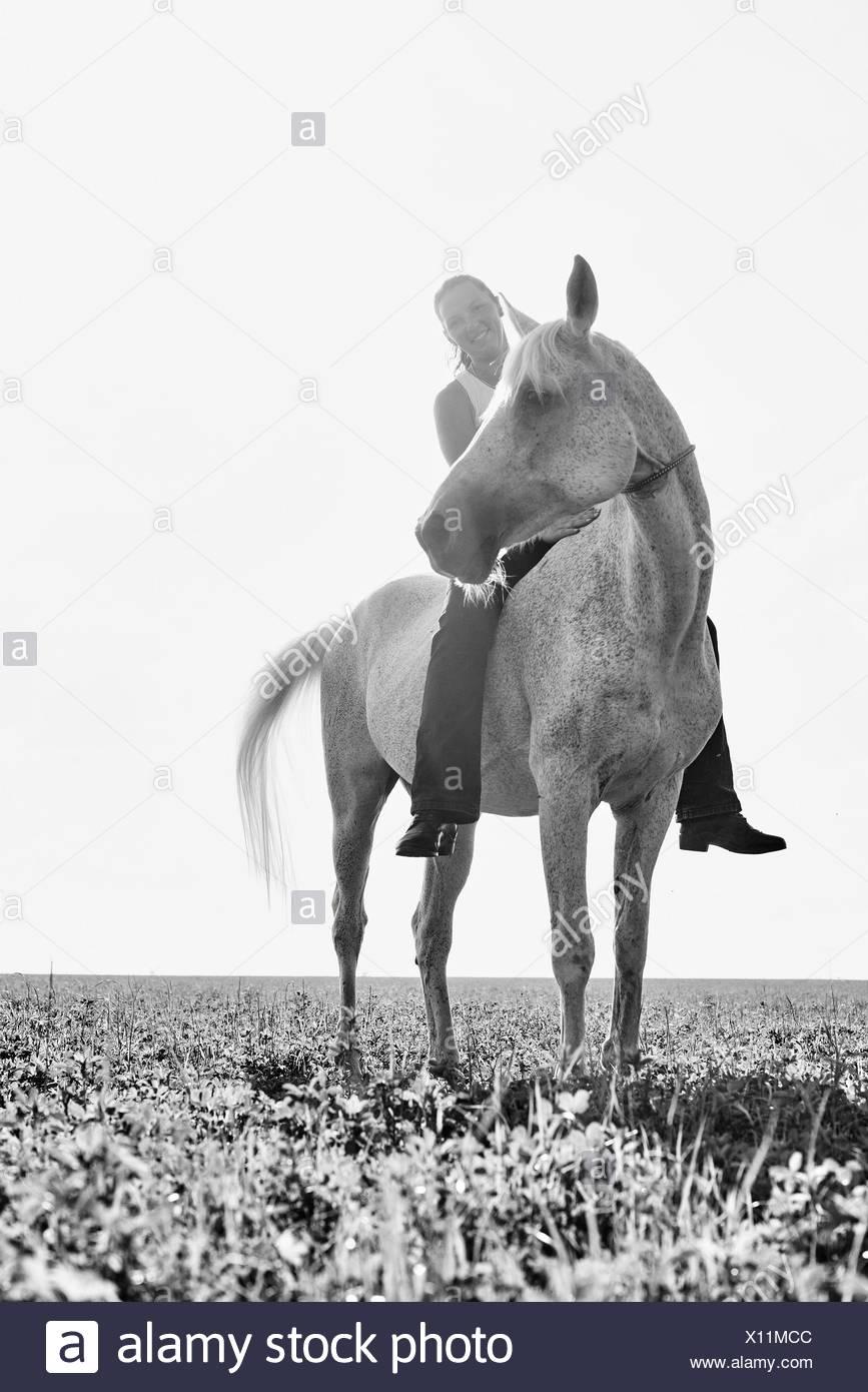 B&W retrato de mujer en caballo bareback en campo Foto de stock