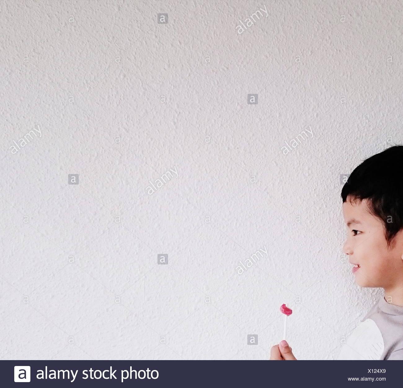 Vista lateral de un sonriente niño sosteniendo la mitad comido lollipop Imagen De Stock