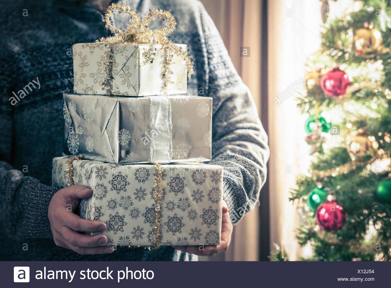 Persona sosteniendo la pila de regalos de Navidad Imagen De Stock