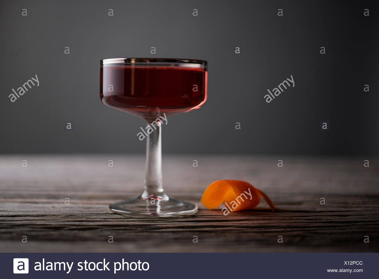 En un sofisticado cóctel vintage, forrada de plata, coupé de vidrio con cáscara de naranja sobre una superficie de madera rústica, de color gris. Foto de stock