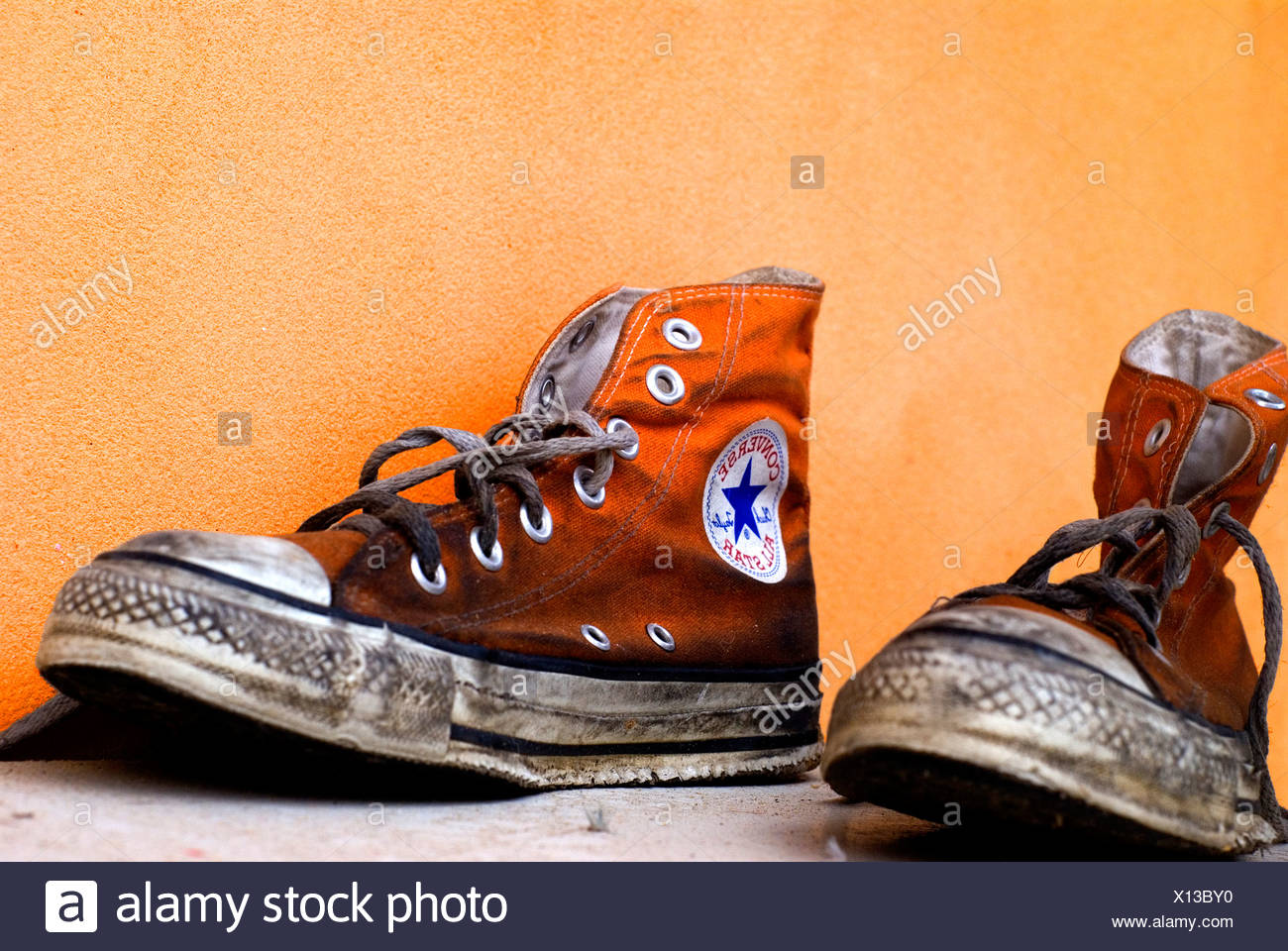 d6d3791b602 Viejas y sucias zapatos Converse All Star naranja sobre un fondo naranja