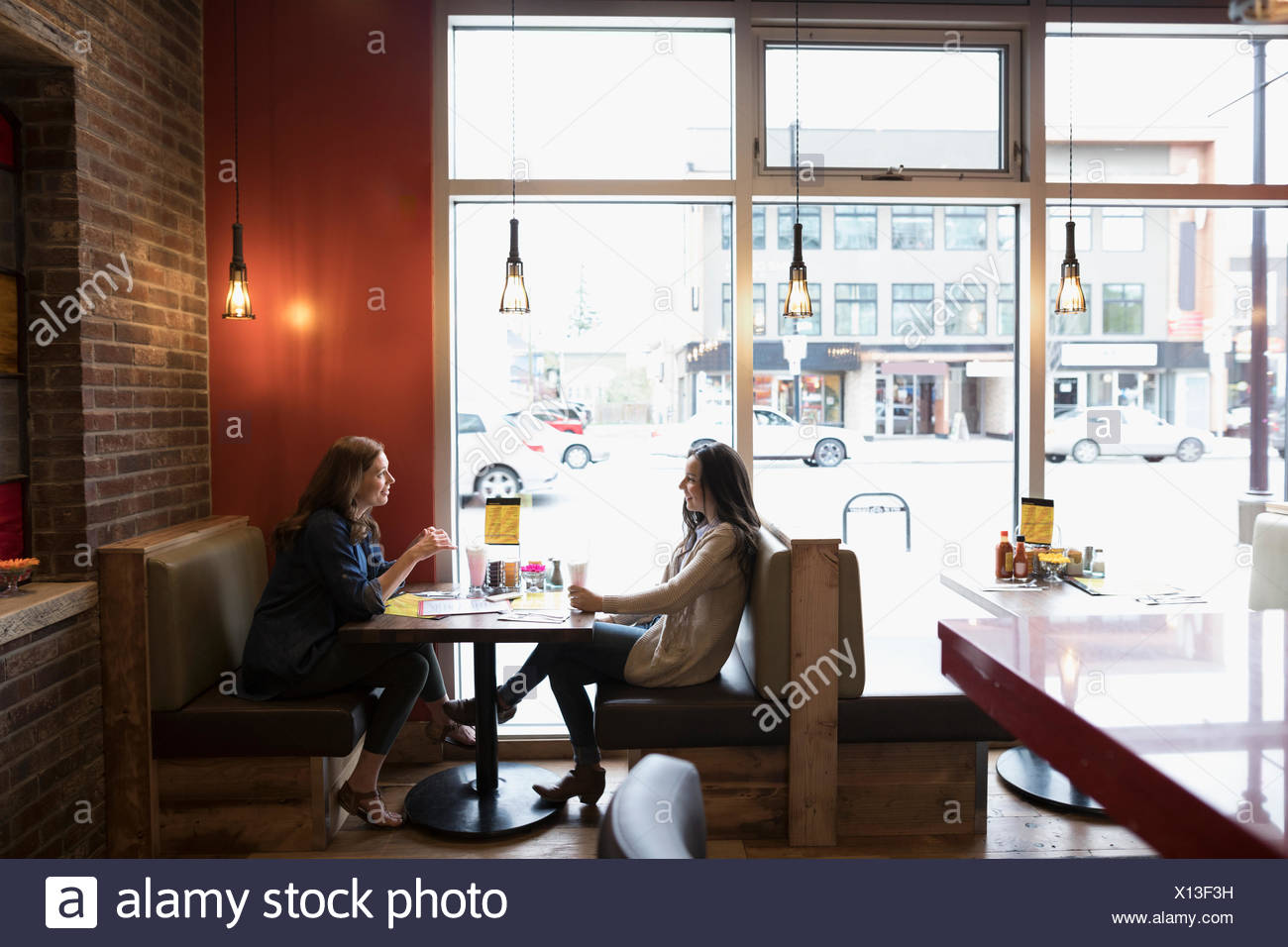 Madre e hija adolescente hablar, comer en diner booth Imagen De Stock