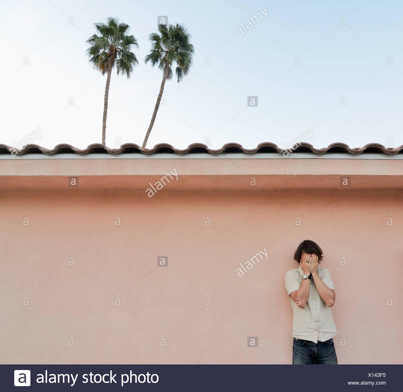 El hombre que cubre su rostro al aire libre Imagen De Stock