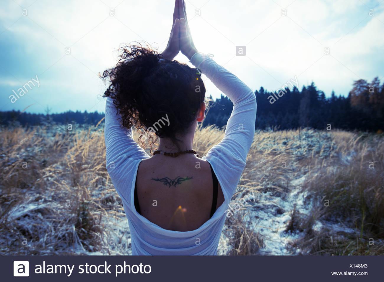 Mitad mujer adulta practicando yoga árbol permanente plantean Foto de stock