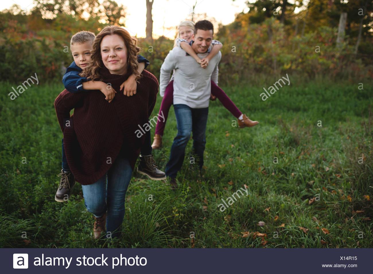 Los padres que dan a los niños piggy back en el campo Imagen De Stock