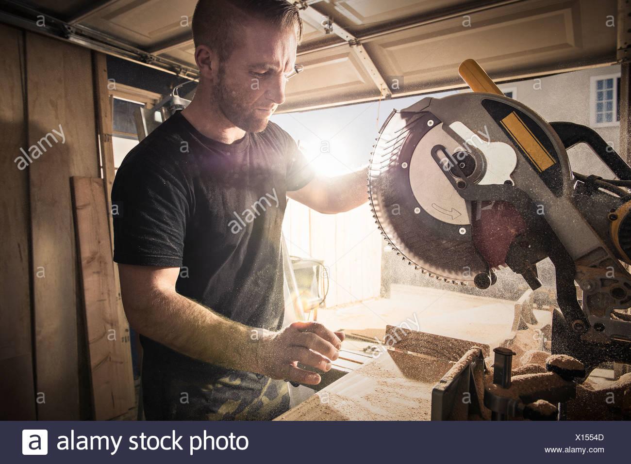 Carpintero macho trabaja con una sierra giratoria en el taller Imagen De Stock
