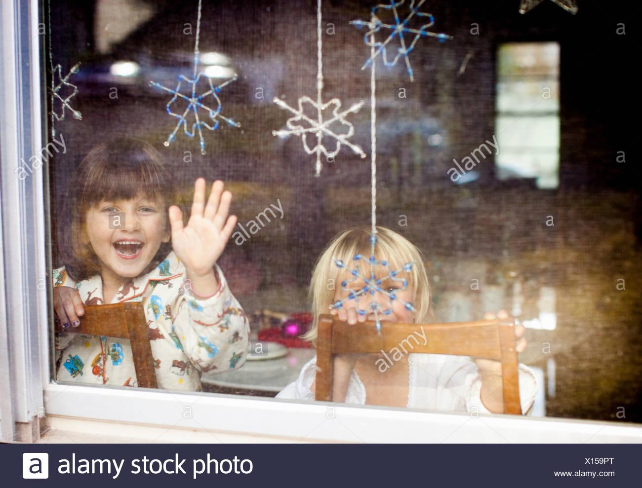 Niños riendo y ondeando en la ventana con copos colgantes Imagen De Stock