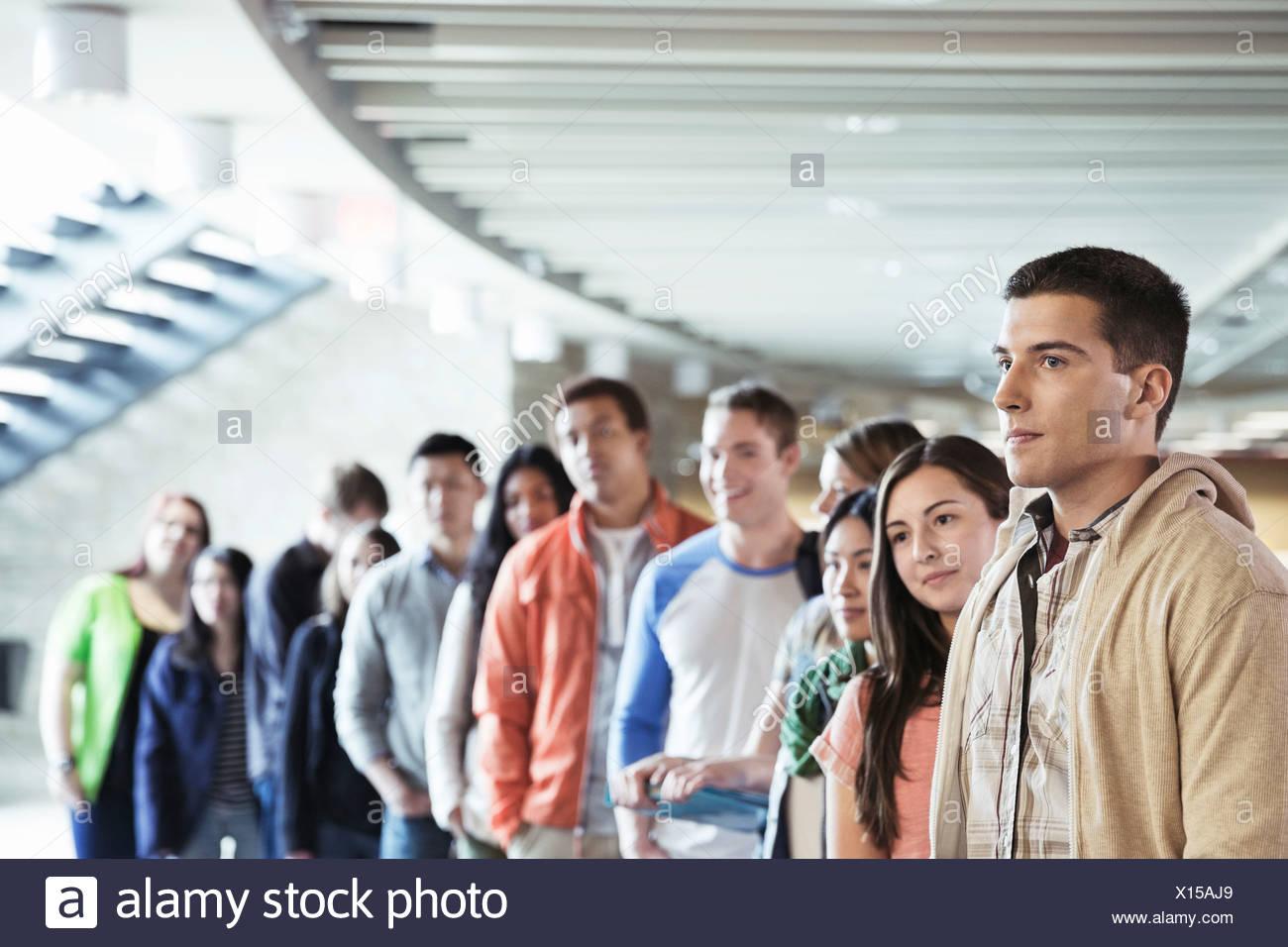 Gran grupo de estudiantes de pie en línea en campus universitario Imagen De Stock