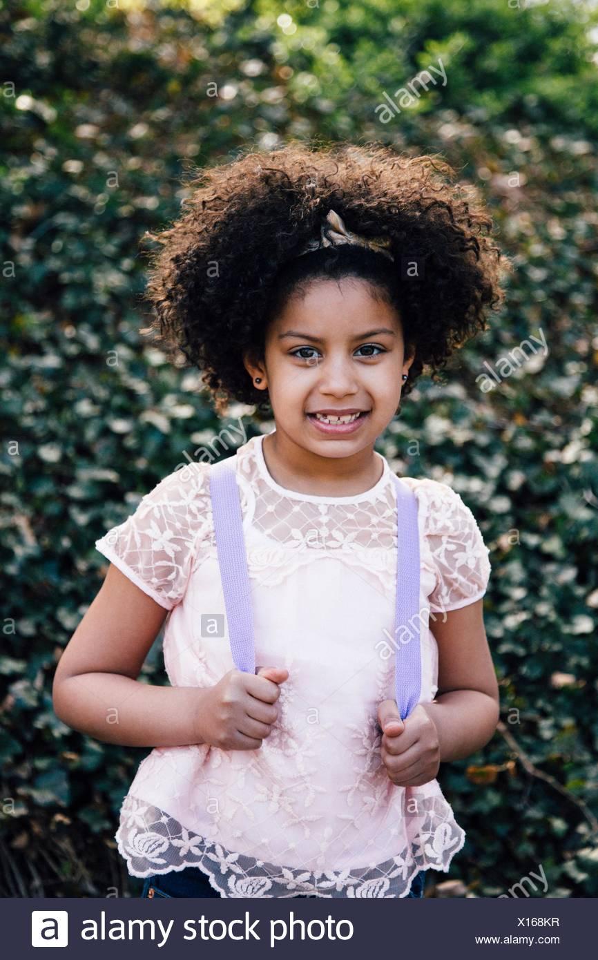 Cintura para arriba retrato de chica que llevaba la mochila, mirando a la cámara sonriendo Imagen De Stock