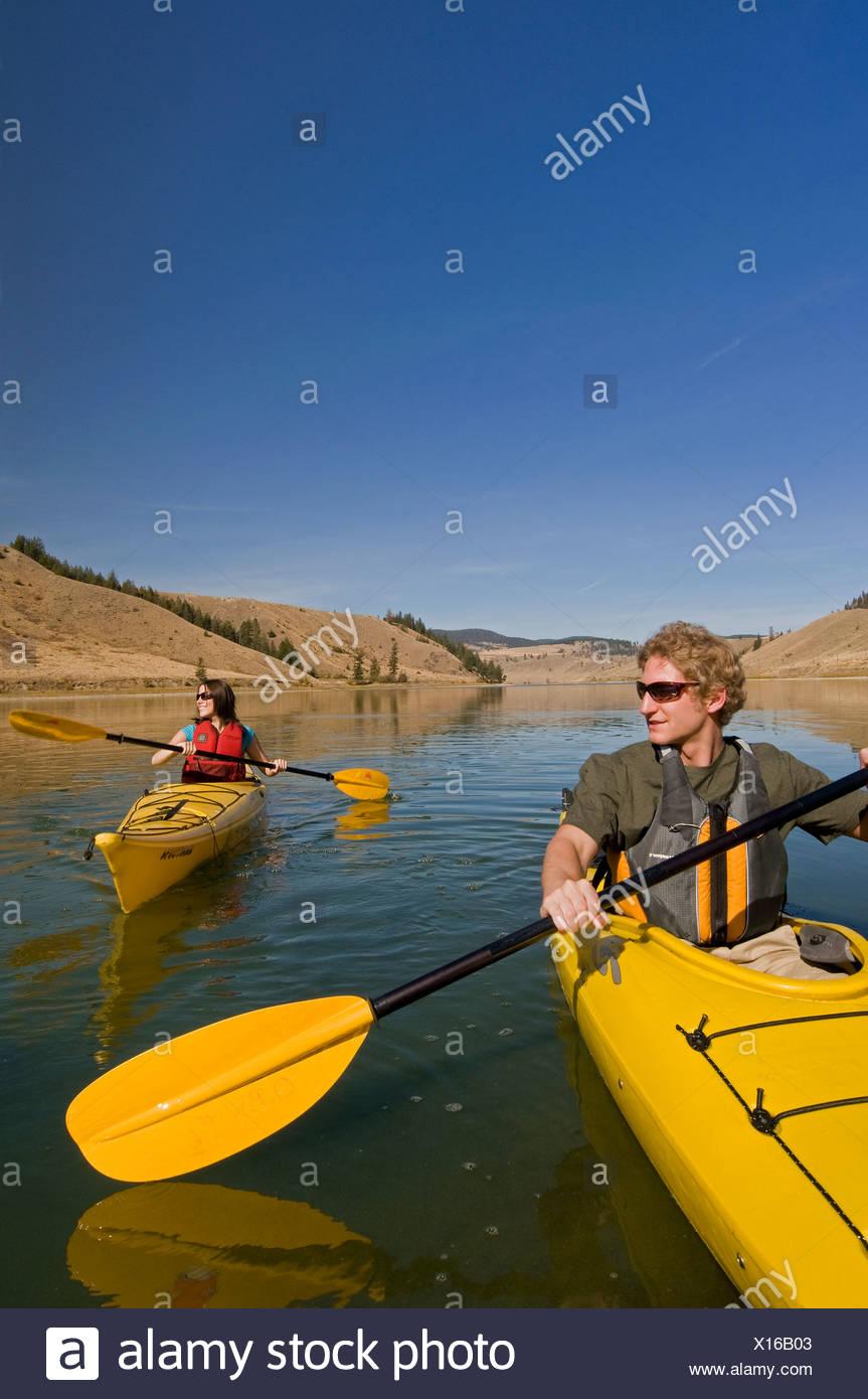 Una joven pareja disfruta de un espectacular día de kayak en el lago Trapp, justo al sur de Kamloops, British Columbia, Canadá Imagen De Stock