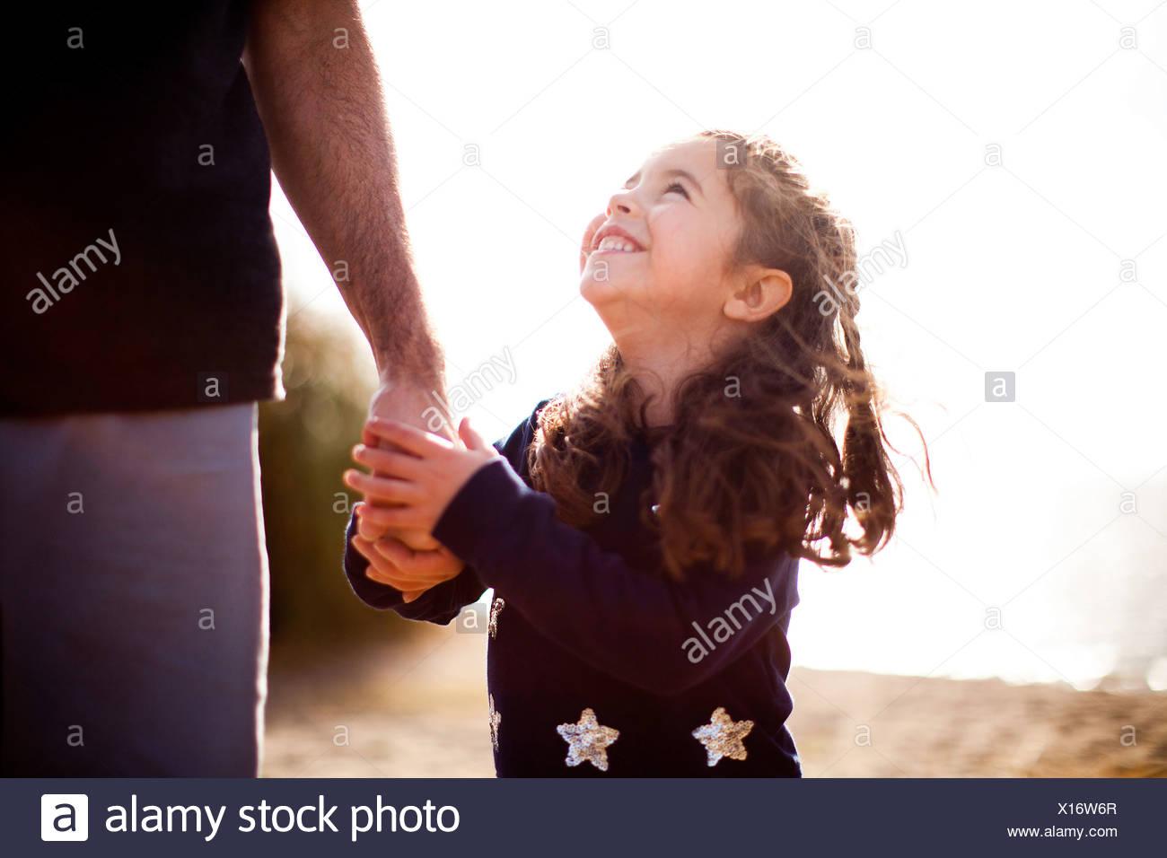 Chica sujetando la mano del padre, mirando hacia arriba Imagen De Stock