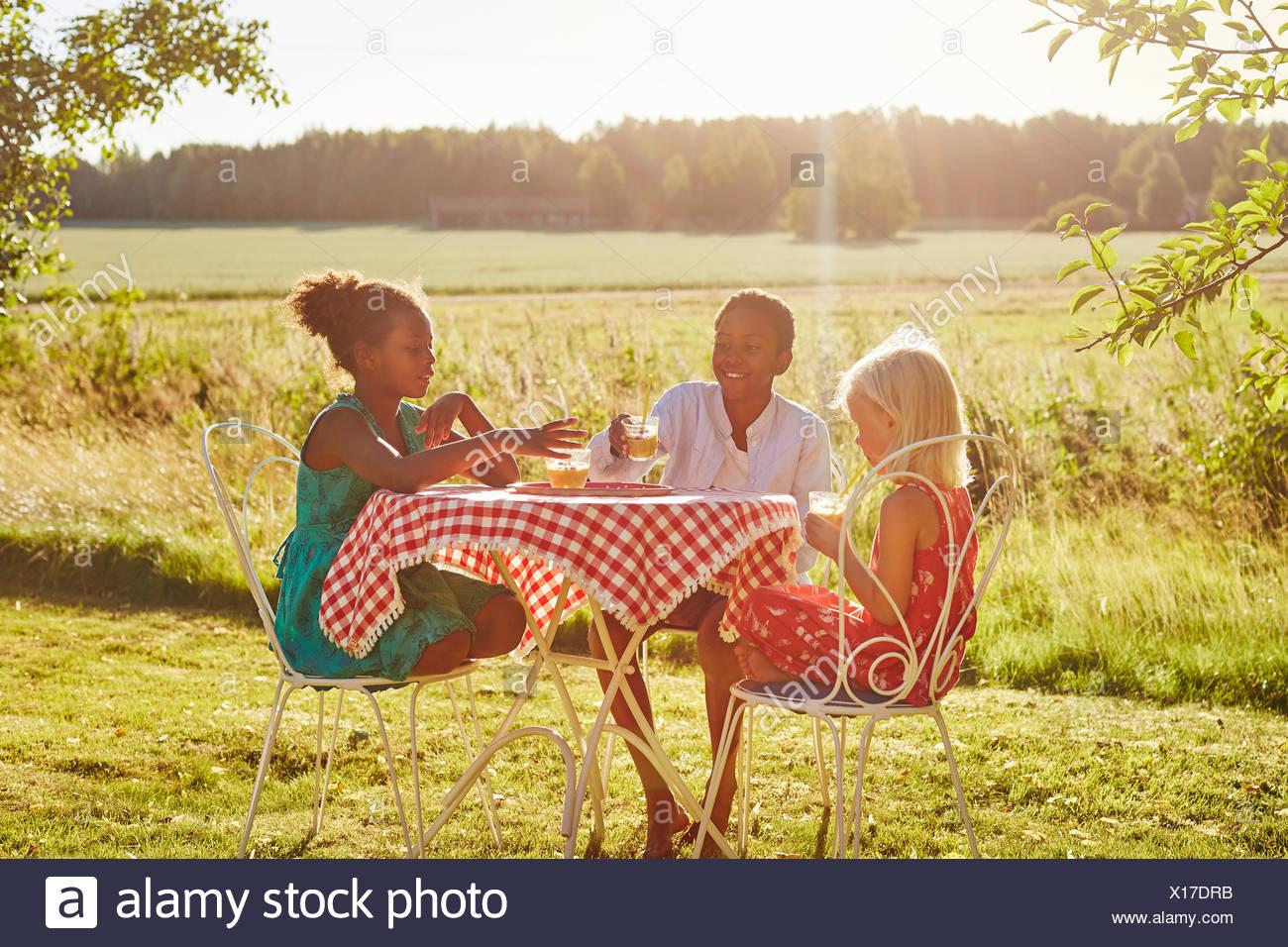 Los niños en una mesa fuera Imagen De Stock