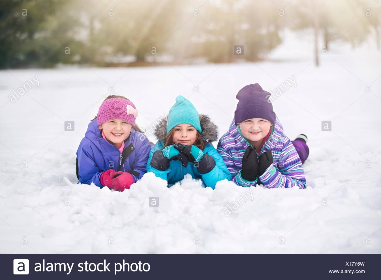 Amigos vistiendo tejer sombreros tumbado en la parte delantera de lado a lado en la nieve mirando a la cámara sonriendo Imagen De Stock