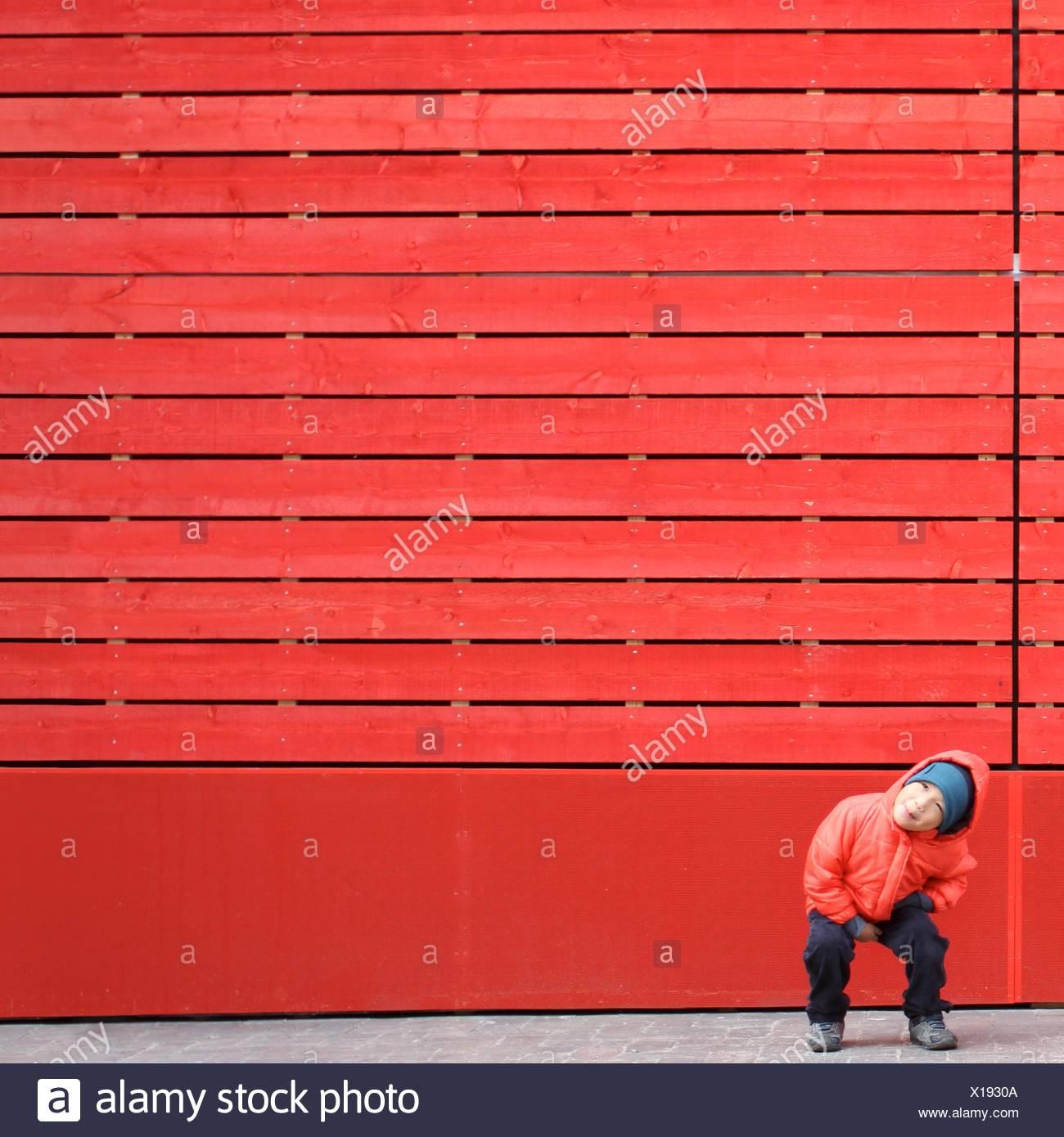 Boy en rojo jugando delante de una pared roja Imagen De Stock