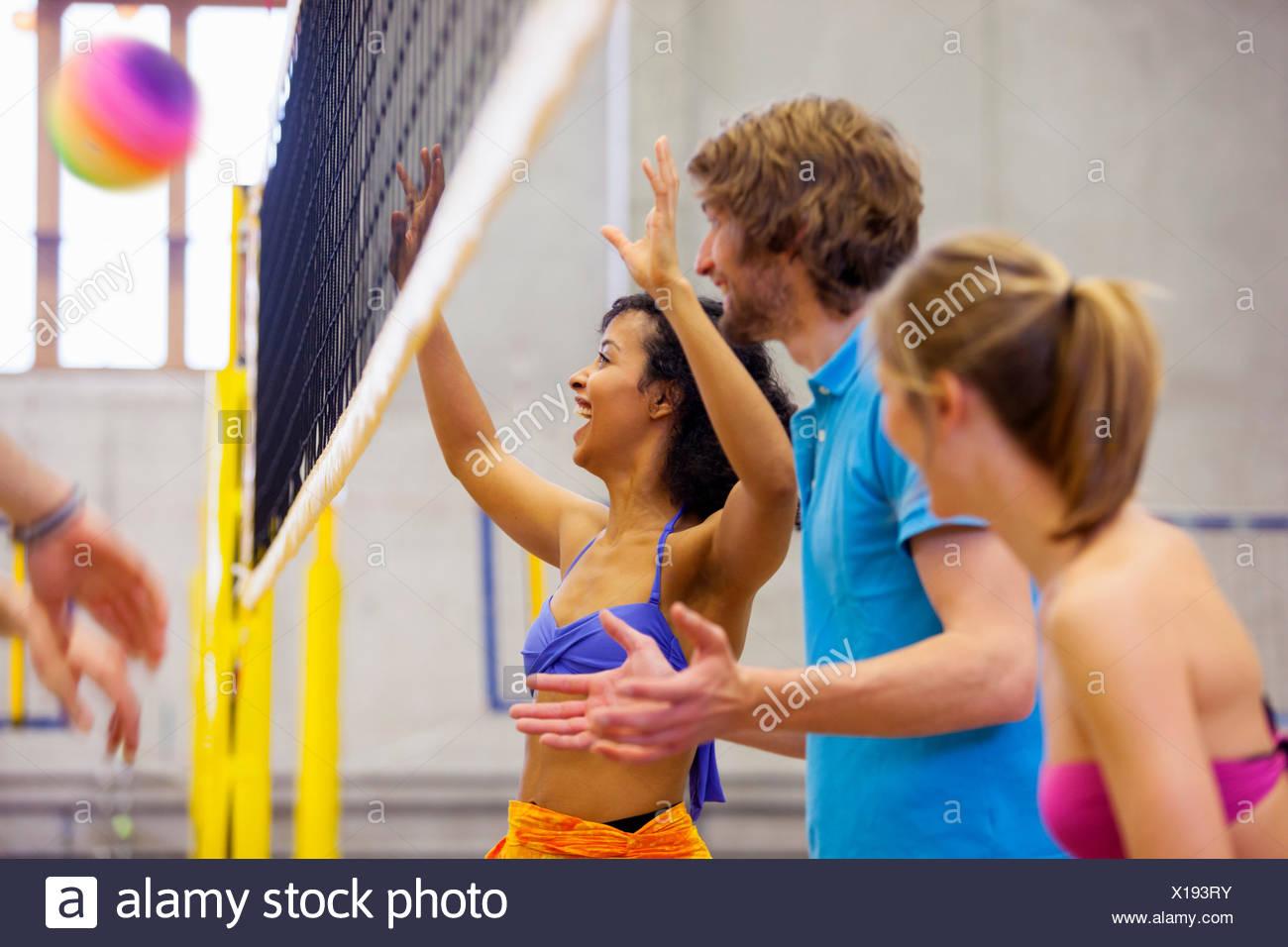 Amigos disfrutando de voleibol de playa en interiores Imagen De Stock