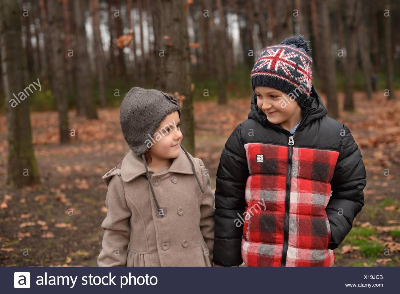 Hermano y hermana (6-7) (4-5) caminando en el bosque Imagen De Stock