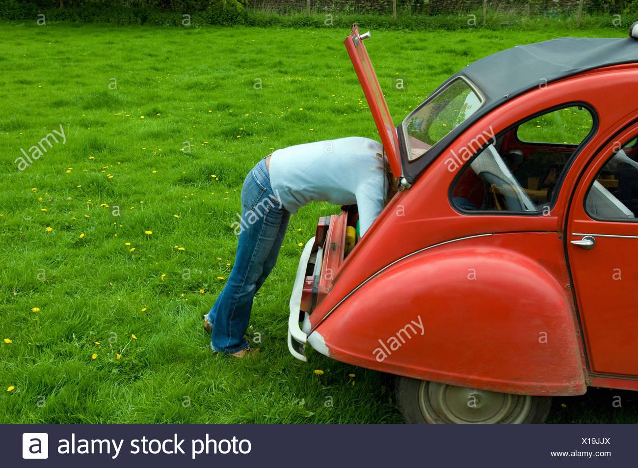 Una persona recostada en el maletero en la parte trasera del coche. Imagen De Stock