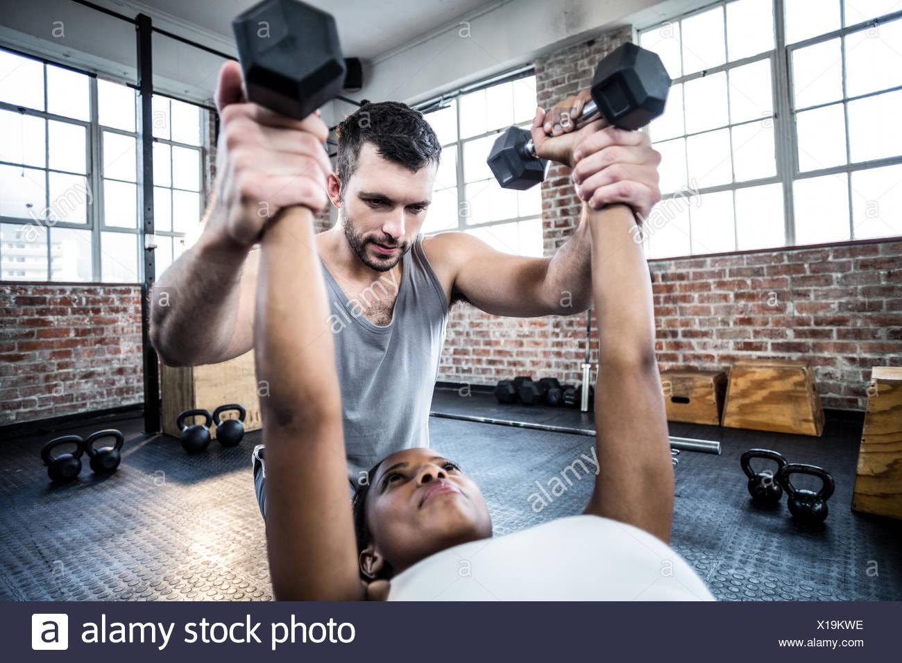 Entrenador personal trabajando con el cliente mantiene pesa Imagen De Stock