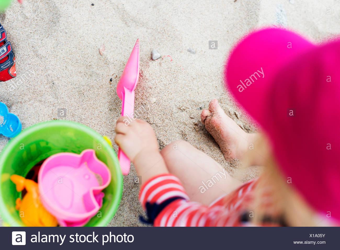 Un alto ángulo de vista de niña jugando con juguetes de arena en la playa Imagen De Stock