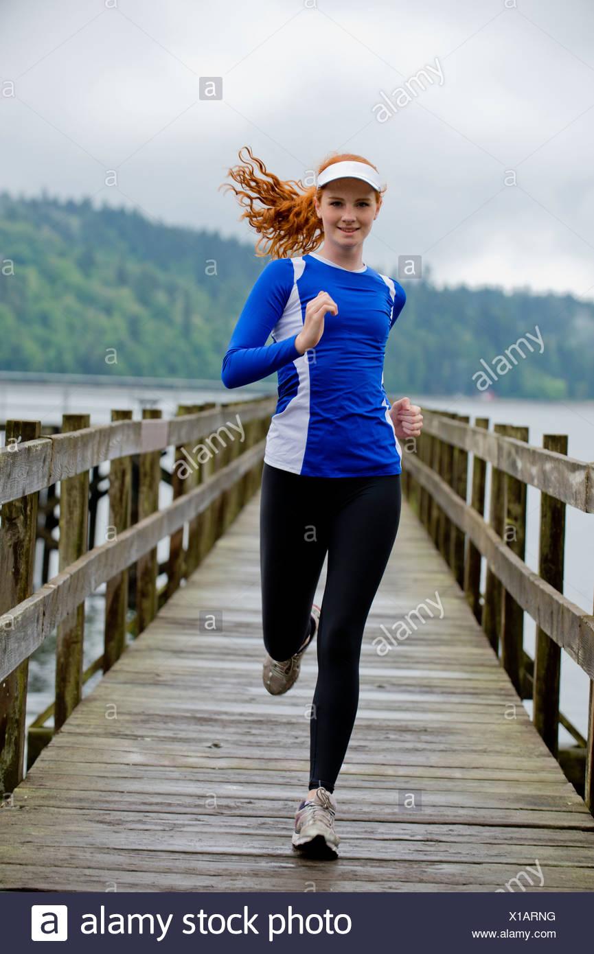 Adolescente corriendo en el muelle, Bainbridge Island, Washington, EE.UU. Imagen De Stock