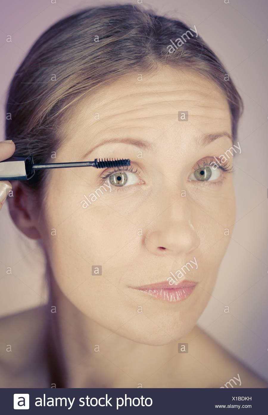 Una mujer de mediana edad de aplicar el rímel Imagen De Stock