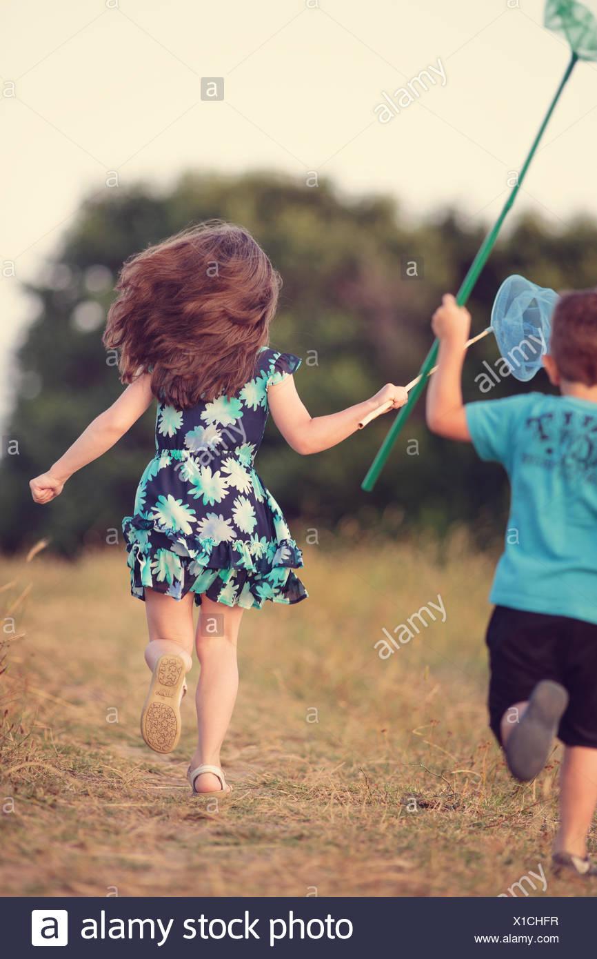 Niño y niña persiguiendo mariposas, Sinemorets, Burgas, Bulgaria Foto de stock