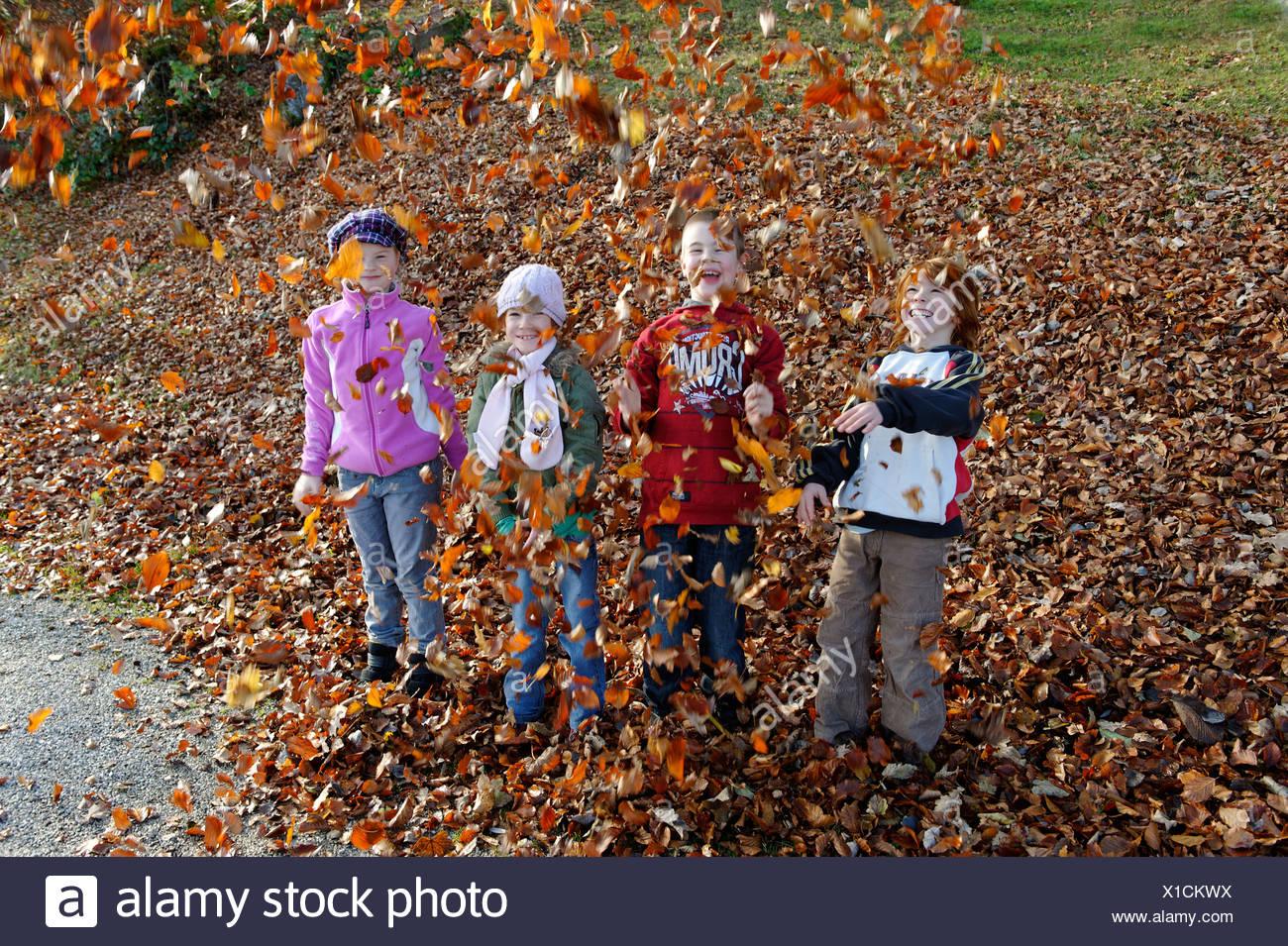 Niños jugando con hojas en otoño Imagen De Stock