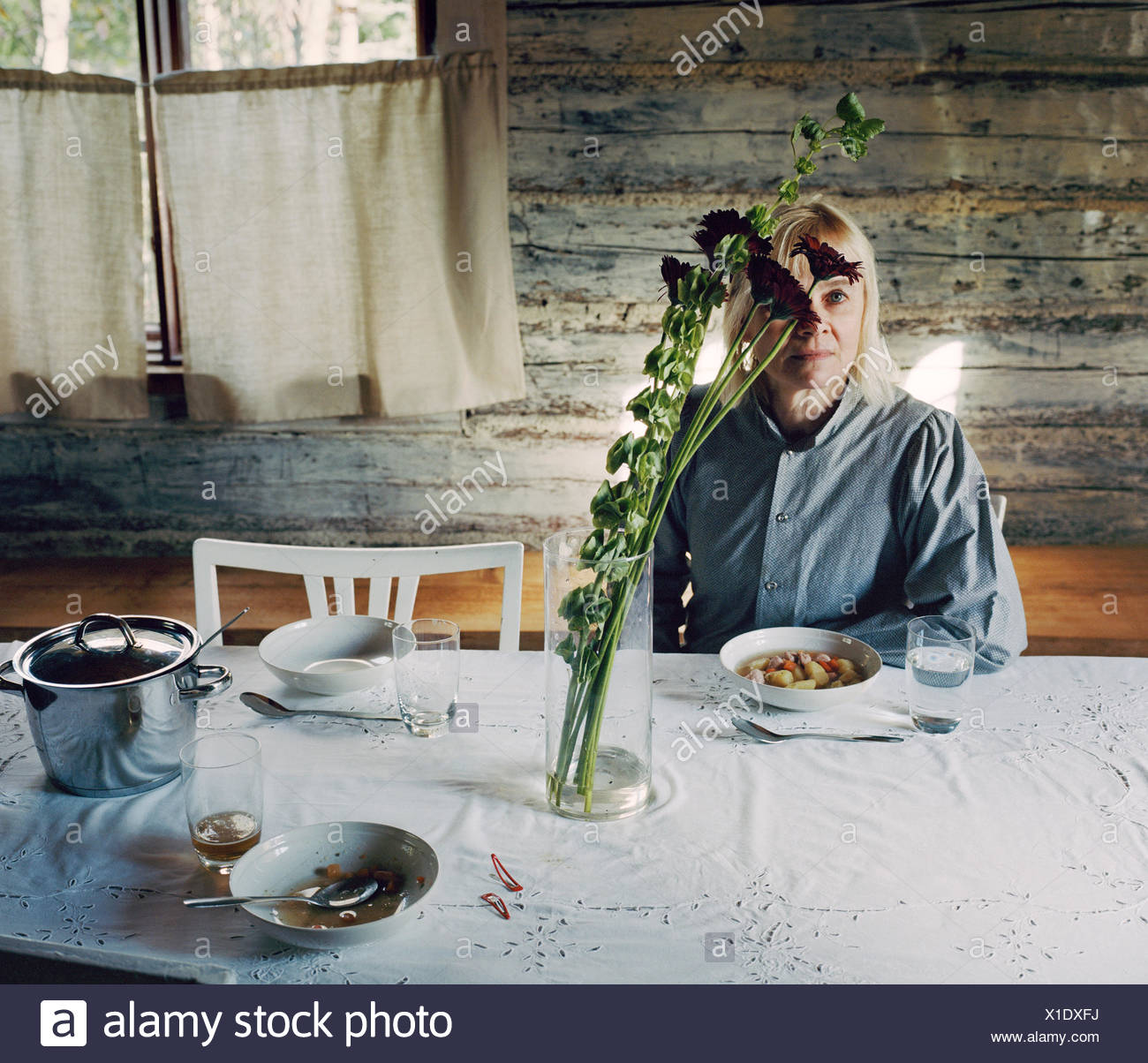 Finlandia, Madura mujer sentada en la mesa Imagen De Stock