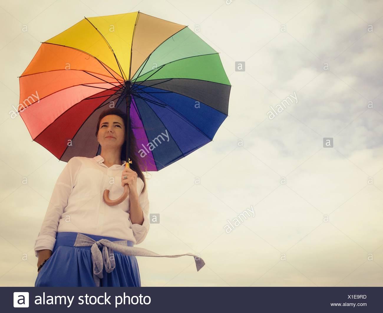 Ángulo de visión baja de hermosa mujer de pie con paraguas multicolores contra el cielo nublado Imagen De Stock