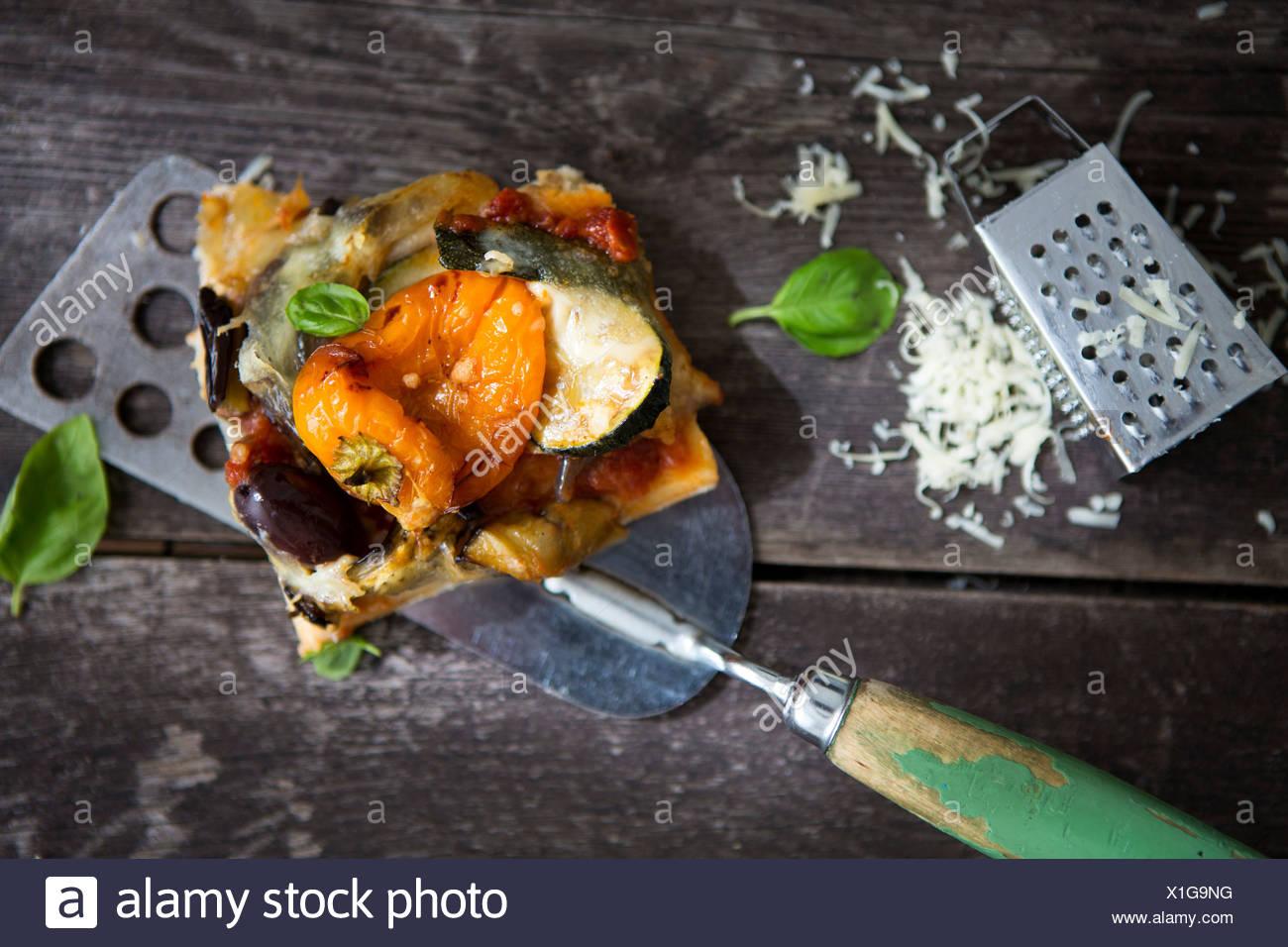 Una porción de pizza casera con pimiento, calabacín, aceite de oliva y albahaca y un rallador de queso Imagen De Stock