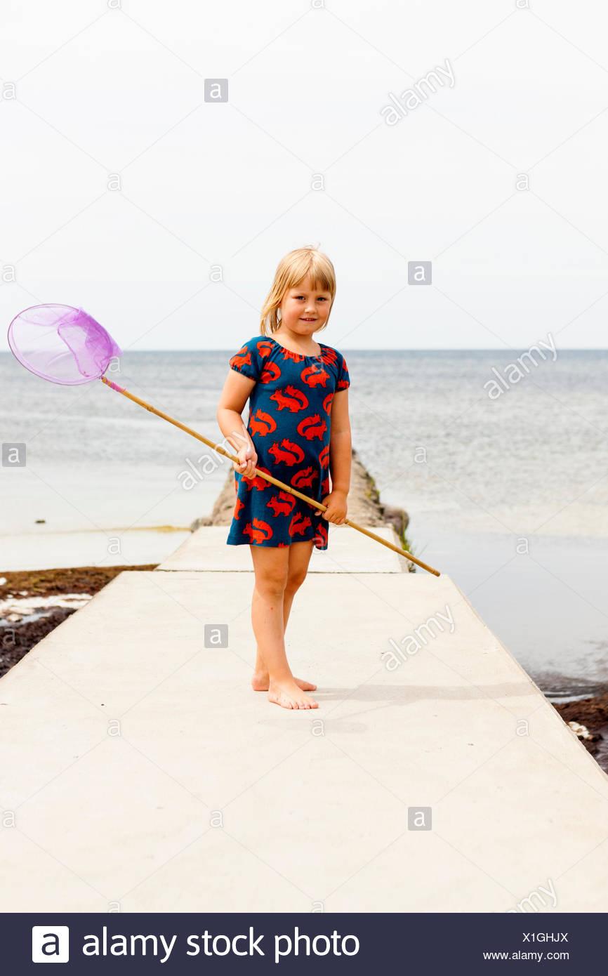 Suecia, Öland, Gronhogen, Chica (6-7) de pie sobre jetty con red de pesca Imagen De Stock