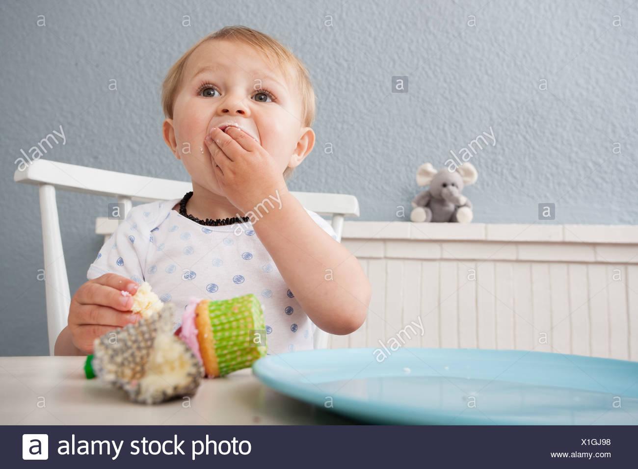 Baby Boy comiendo cupcake Imagen De Stock