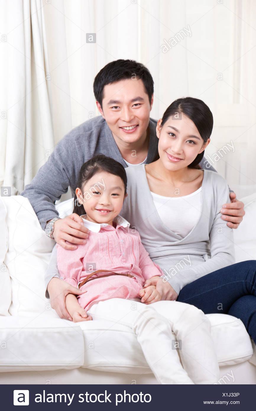 Familia joven sentado en el sofá Foto de stock
