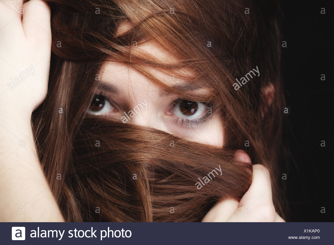 Mujer cubre el rostro por largos pelos marrones Foto de stock