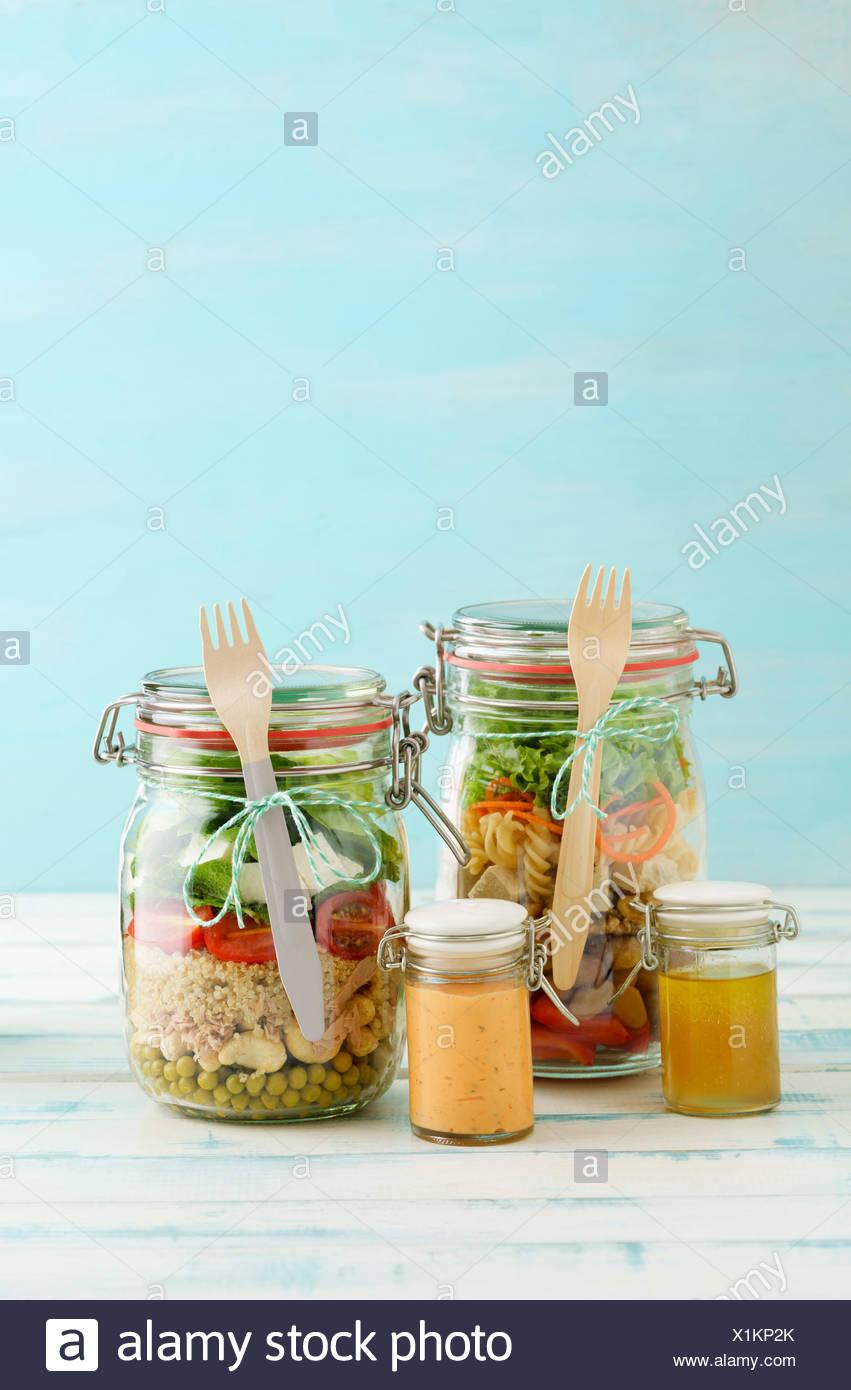 Salate zum Mitnehmen Glas im mit Erbsen, Cashew-Nüssen, Thunfisch, cuscús, Cocktailtomaten, Minze, Schafskäse, Blattsalat und vinagreta, roter PAP Foto de stock