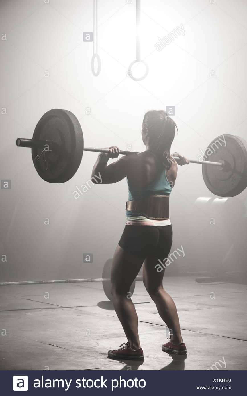 Mujer joven levantando barbell, vista trasera Imagen De Stock