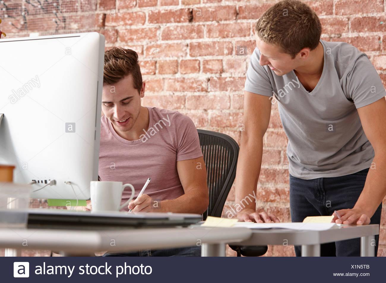Los hombres jóvenes hablando y escritorio con ordenador Imagen De Stock