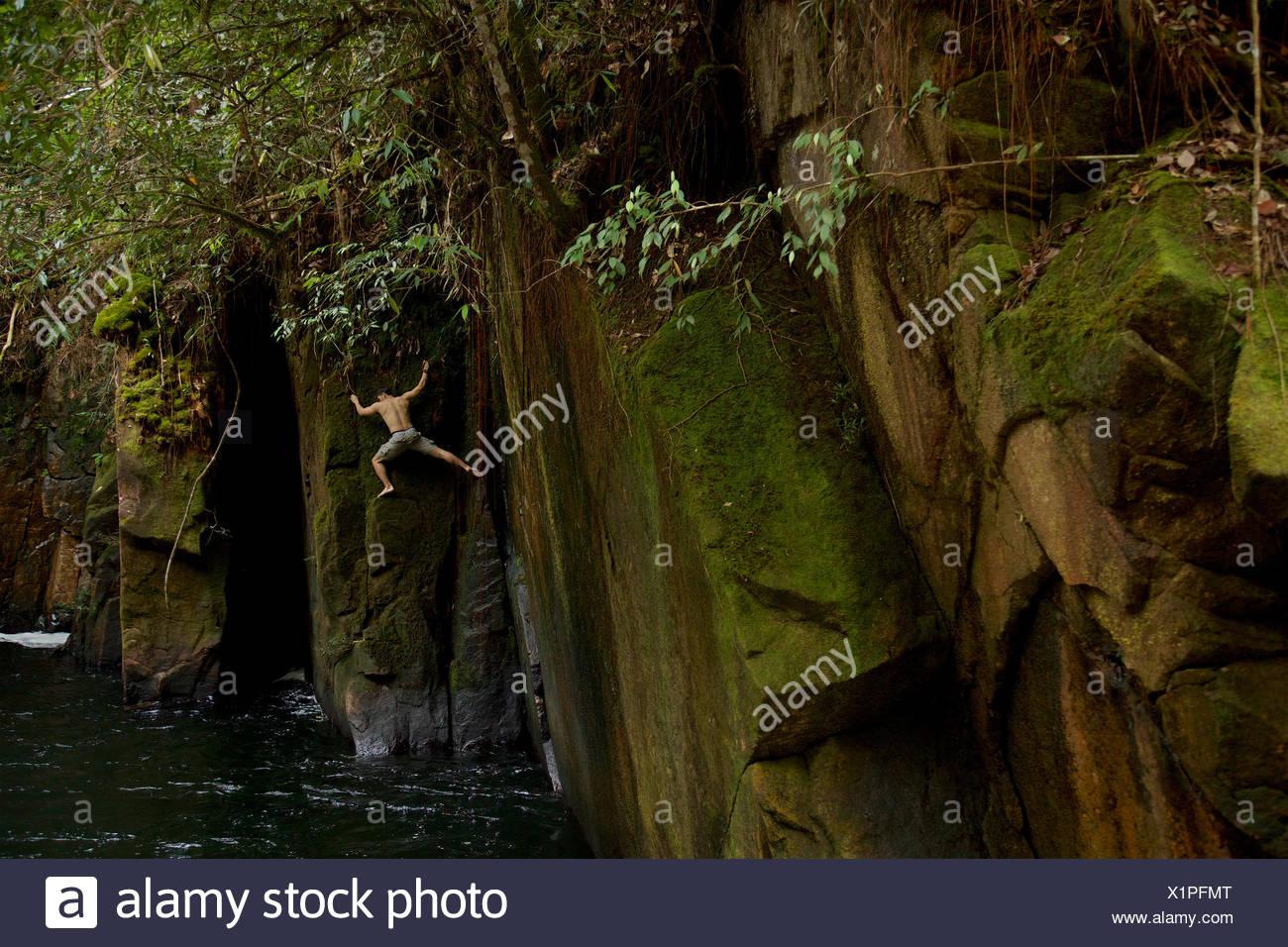 Un hombre haciendo agua profunda sin individualizar en los acantilados de la quebrada abajo Riam, o el canal Parit Falls, una inusual la ranura en la parte superior de la cascada Río Siduk. Imagen De Stock