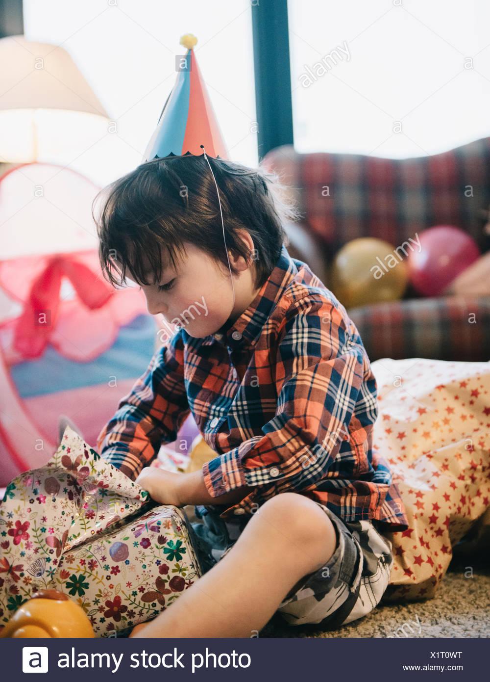 Un niño desenvolver sus regalos en su fiesta de cumpleaños. Imagen De Stock