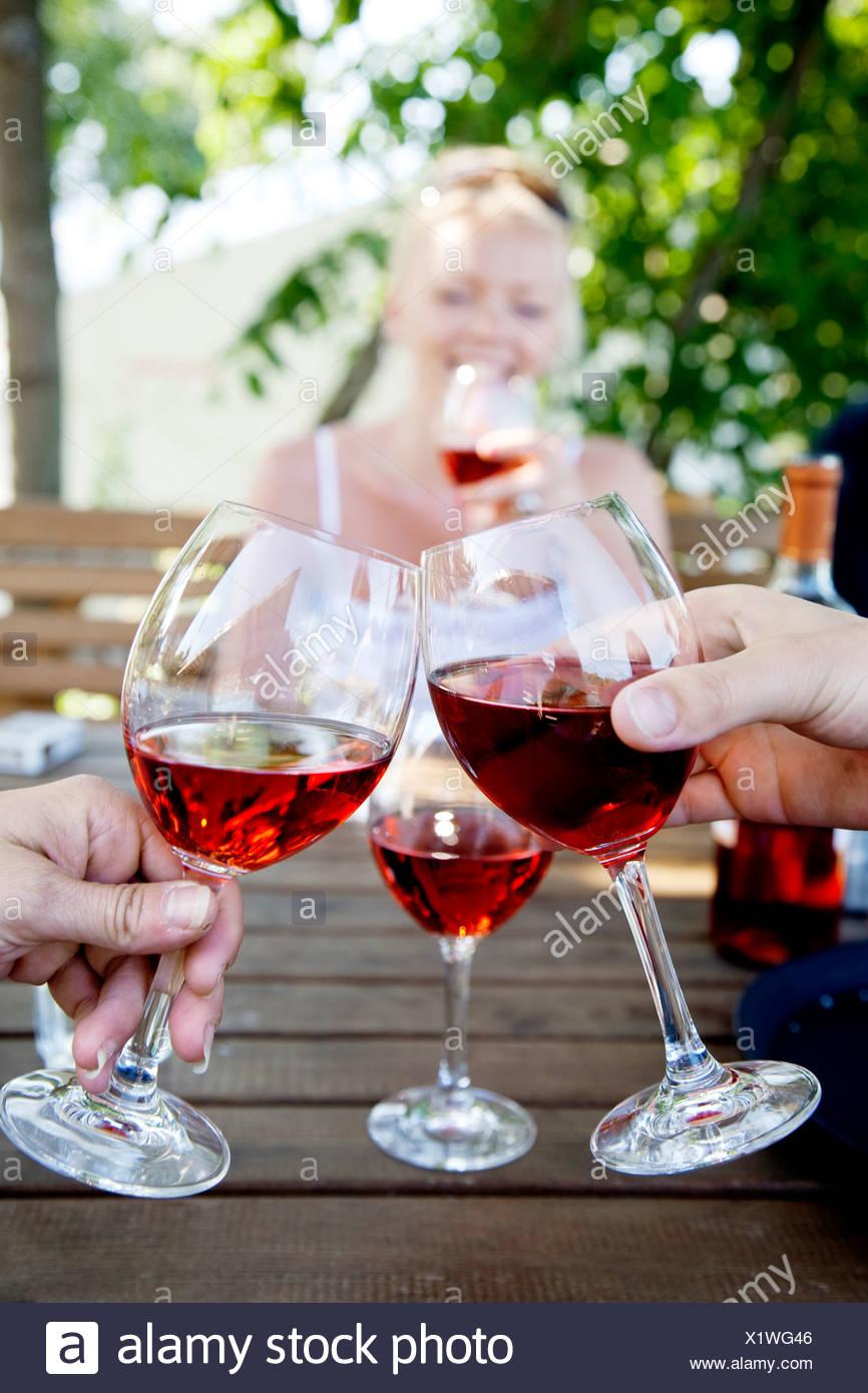 Las manos del hombre brindando con copas de vino Imagen De Stock